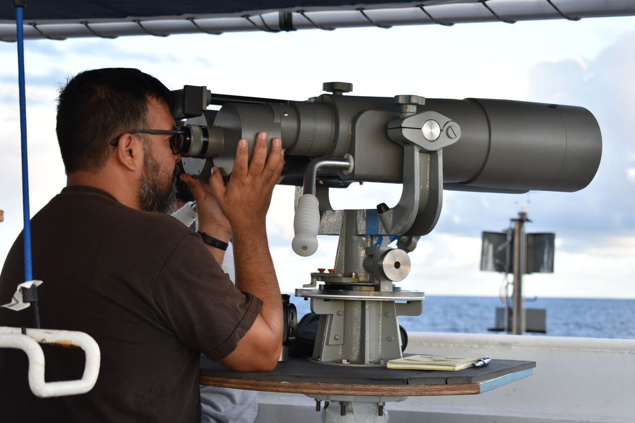 "Senior Observer Ernesto Vázquez uses ""big eye"" binoculars to search for cetaceans. Credit: NOAA Fisheries/Staci DeSchryver."