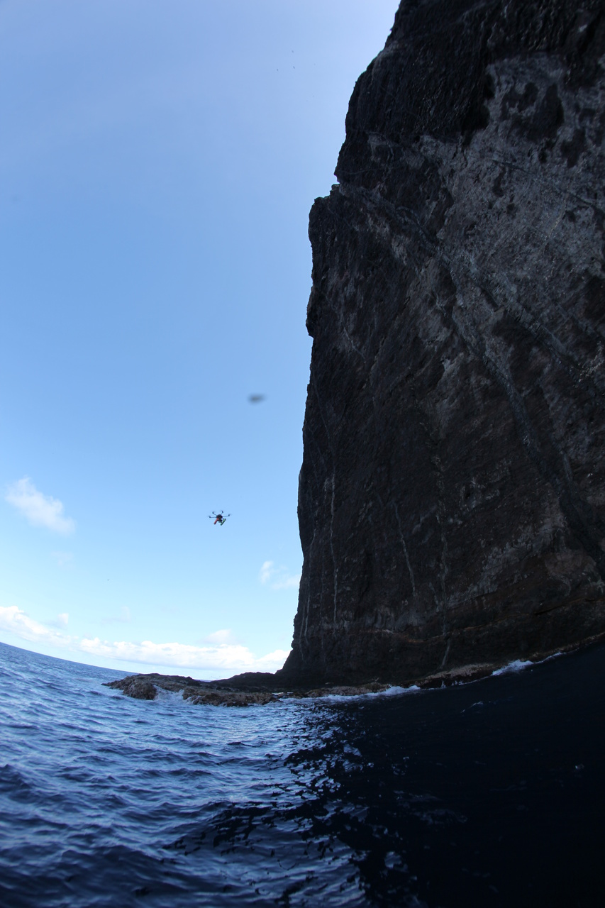 An unmanned aerial system (UAS) hovers near the cliff edge of Nihoa.