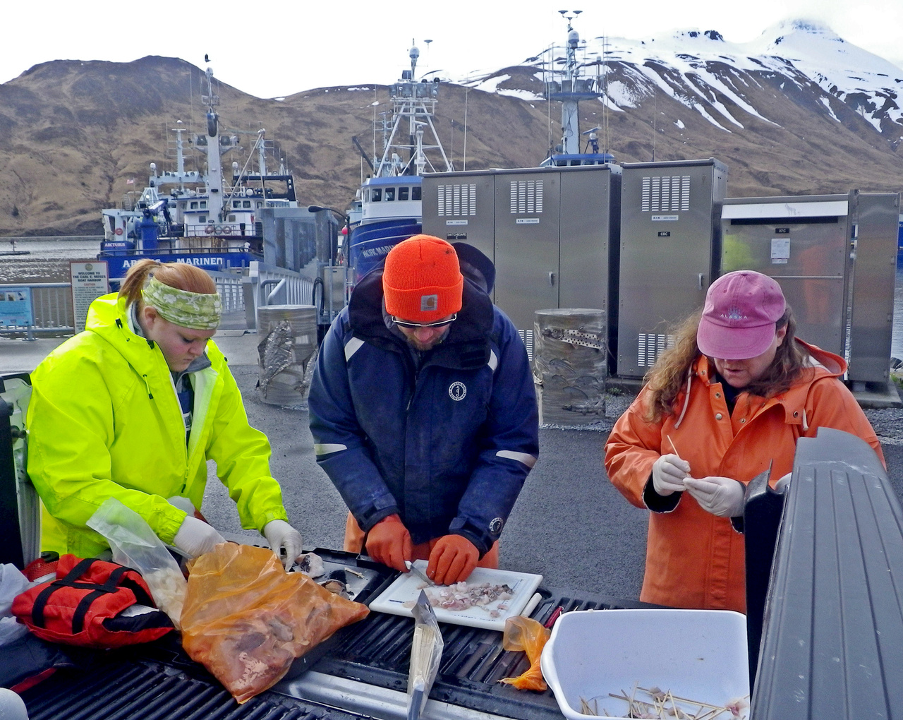 Sarah Johnson (Alaska Department of Fish and Game Observer) (left), Jeff Cox (Bering Sea Fisheries Research Foundation), Pam Jensen (NOAA Fisheries) preparing food for crab. Sarah, Jeff and Pam are cutting cod scraps into chunks and threading them onto bamboo skewers. The skewers keep the pieces of cod from washing out of the nets as they are lowered into the water.