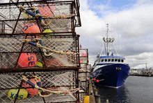 Crab and lobster pots and commercial vessel at dockside.